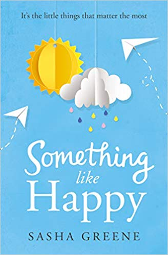 Cover of the book Something Like Happy, showing a paper cut out of a yellow sun and a white cloud hanging against a blue background, with two paper planes leave trails at left and right. At the top of the cover in black letters: 'It's the little things that matter the most'. At the bottom, cursive letters in white spell out 'Something Like Happy' and below that black capitals say 'Sasha Greene'.