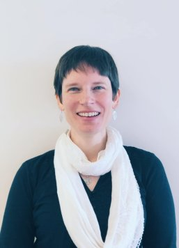 This is a picture of me. I am against a white background and I have dark brown hair cut in a pixie cut and I am smiling enough to show my teeth. I have silver leaf earrings, a plain navy blue top and a white scarf looped twice around my neck.